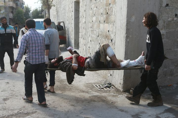 Syrians carry a wounded man after war crafts belonging to the Syrian and Russian army carried out airstrikes over residential