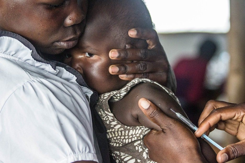 A South Sudan refugee child is immunized and screened by a Medical Teams International clinical officer at the Kuluba Collect