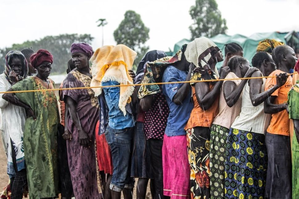 A group of women stand in the rain waiting to be registered and to receive their refugee status at Kuluba Collection Point.<b