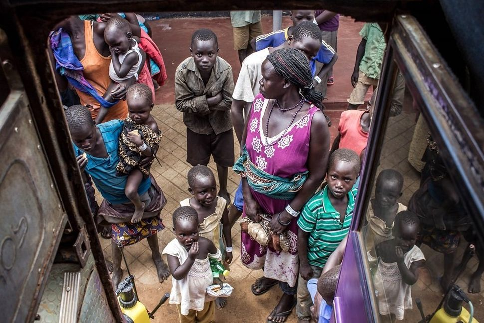 Newly arrived women and children refugees boarding a UNHCR bus at Elegu Collection Point, near the Nimule border -- one of th