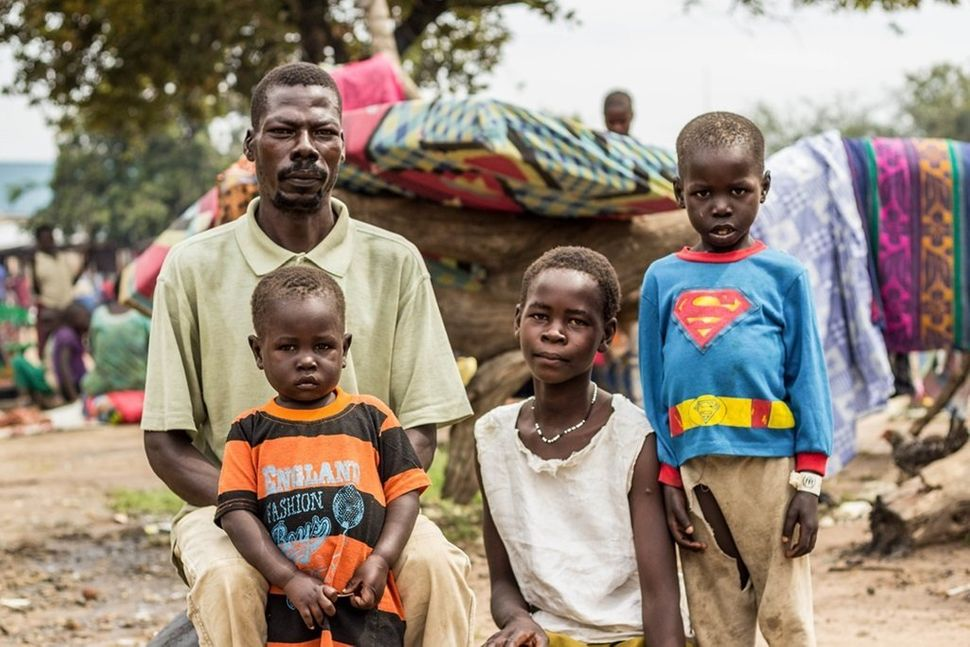 Michael T., 42, and his three children wait to be relocated from the Ocea Reception Centre to the Bidi Bidi refugee settlemen