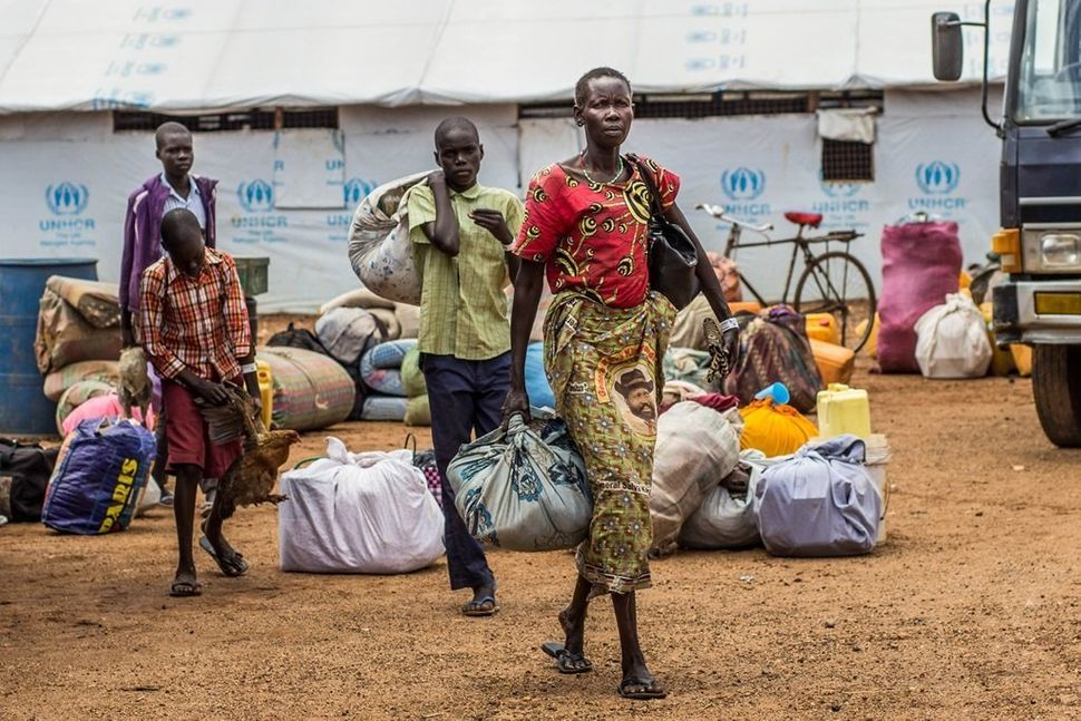 At Elegu Collection Point, a family of refugees carries their luggage for relocation to Bidi Bidi settlement. <i>Location: El