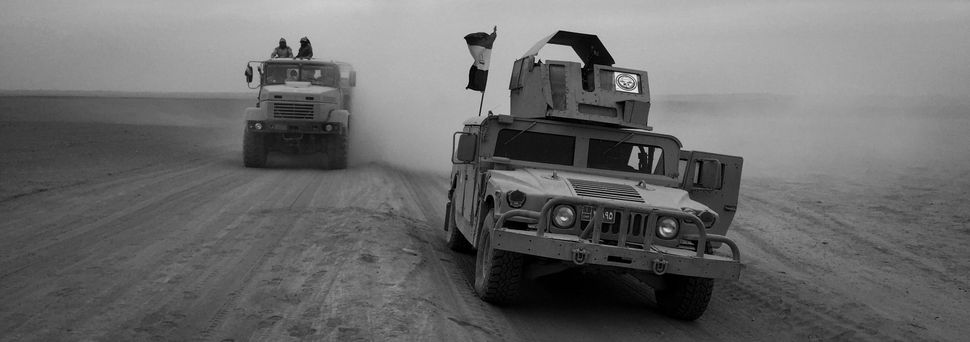 Humvees from the Iraqi Army Armoured Ninth Division are seen on a desert road leading to Mosul on November 15, 2016 in Mosul,