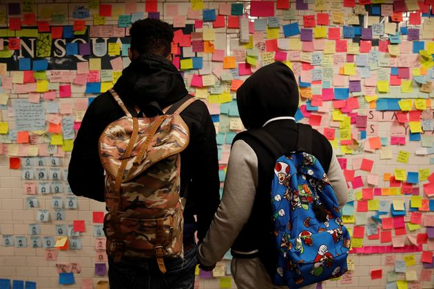 Post-it notes bearing messages of support and anti-Trump slogans cover a wall in New York City's...