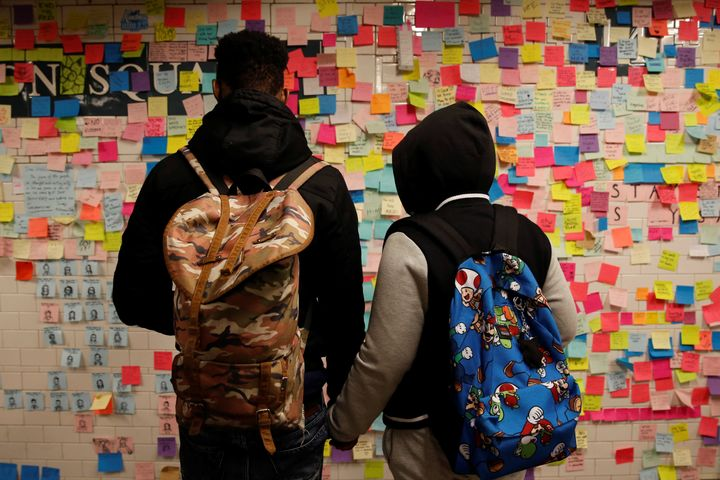 Post-it notes bearing messages of support and anti-Trump slogans cover a wall in New York City's Union Square subway sta