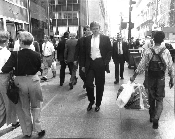 Walking down Fifth Avenue, Donald Trump goes unnoticed by sidewalk crowds during lunchtimeon August 28, 1990.