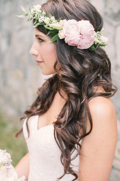 <p>An asymmetrical floral crown calls attention to this bride's to-die-for mane.</p>