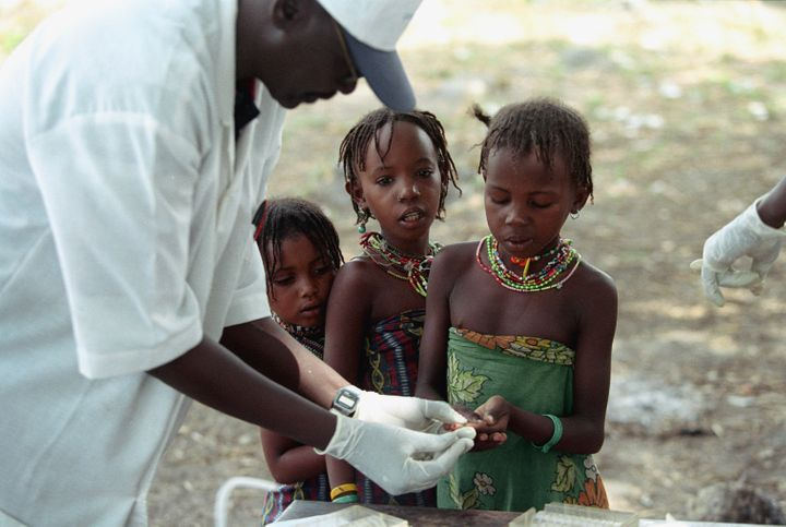 Nomads from the Peul tribe give blood samples to be tested for sleeping sickness, part of an ambitious campaign set up by the