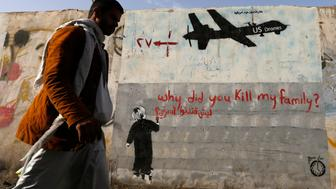 A man walks past a graffiti, denouncing strikes by U.S. drones in Yemen, painted on a wall in Sanaa November 13, 2014. Yemeni authorities have paid out tens of thousands of dollars to victims of drone strikes using U.S.-supplied funds, a source close to Yemen's presidency said, echoing accounts by legal sources and a family that lost two members in a 2012 raid. REUTERS/Khaled Abdullah (YEMEN - Tags: CIVIL UNREST MILITARY POLITICS SOCIETY TPX IMAGES OF THE DAY)