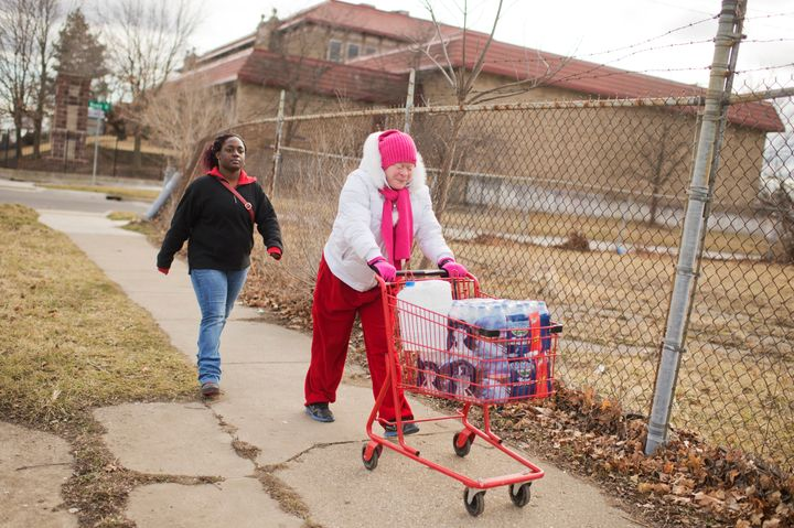 Virginia Mitchell, right, and her daughter-in-law Tiara Williams take bottled water home in February in Flint, Michigan.&nbsp