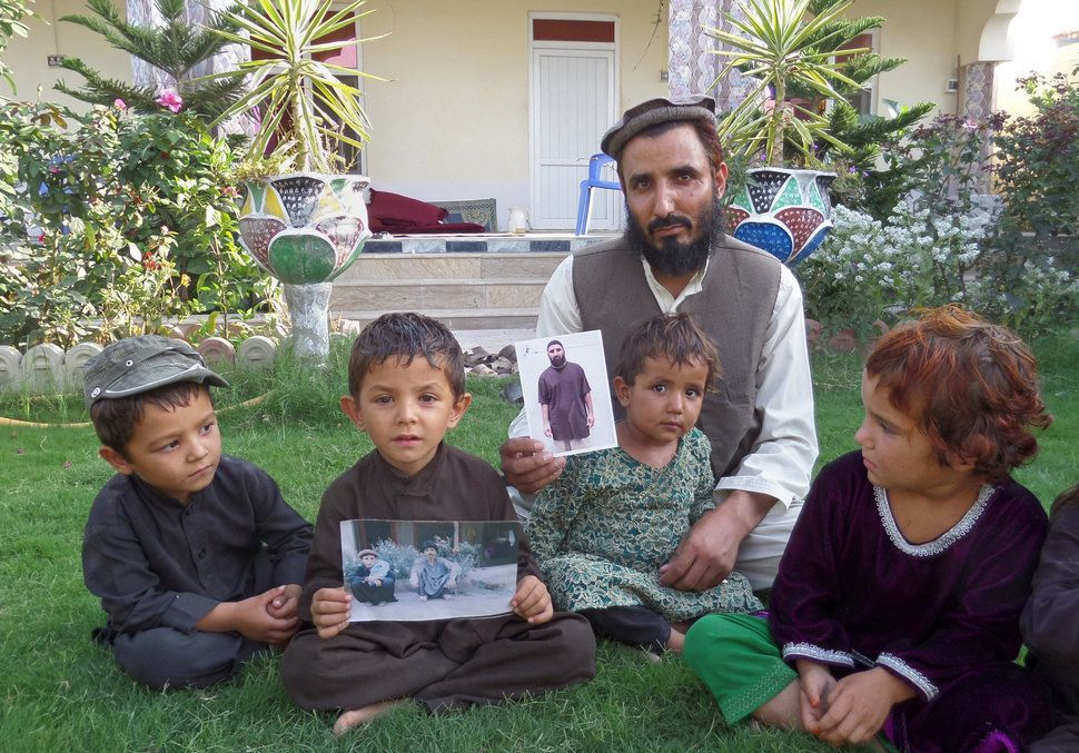 "In this Tuesday, Aug. 16, 2016, photo, Fazel Karim, holds a picture of his brother, who was recently released from the Guantanamo Bay detention center, at his home in the village of Haiderkhil, Mandozai district of Khost province, Afghanistan. Obiadullah's family said they're excited their son is among 15 prisoners released from Guantanamo and transferred to the United Arab Emirates this week. They say Obiadullah is now ""free"" after 14 years in the U.S. prison in Cuba and that they can hardly wait to hear from him. (AP Photo/Nishanuddin Khan)"
