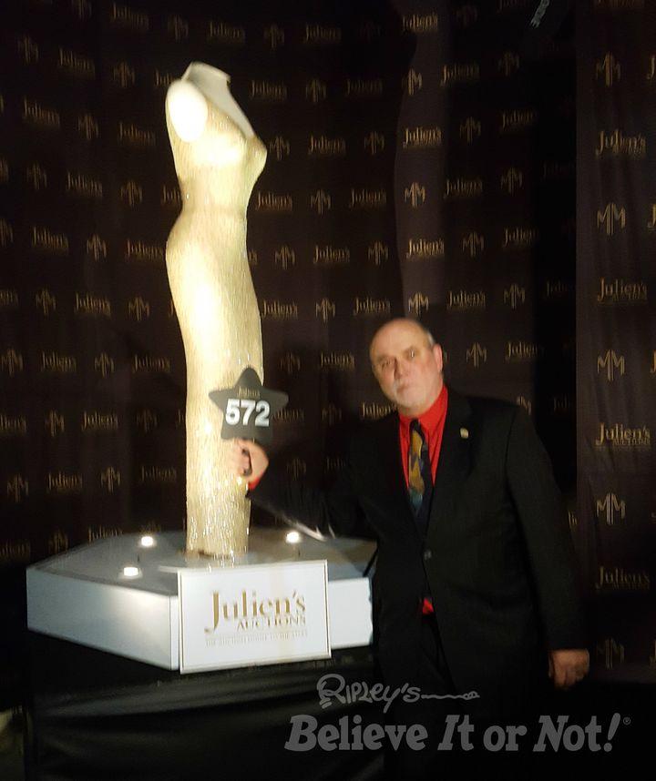 Ripley's Edward Meyer poses next to the dress Marilyn Monroe wore when she sang atPresident John F. Kennedy's birthday.
