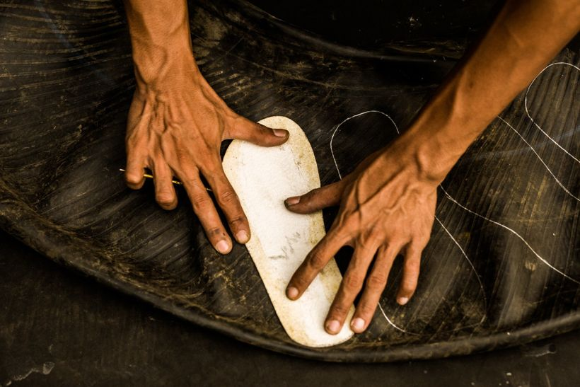 An artisan traces the shape of a sole onto a tire inner tube.