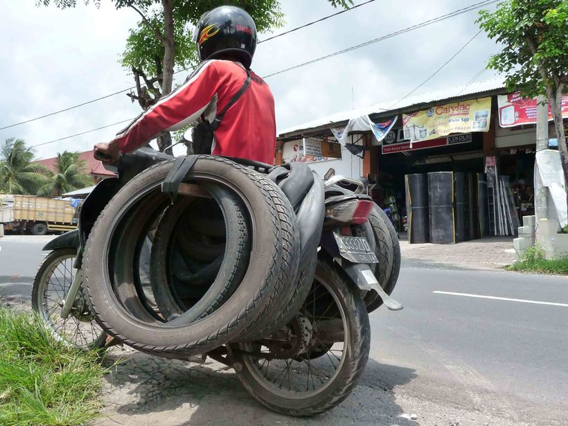 A man collects waste tires in Indonesia, most likely on his way to a tire broker.