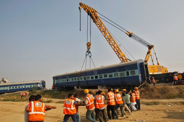 Rescue workers search for survivors at the site of a train derailment in Pukhrayan, south of Kanpur city,...