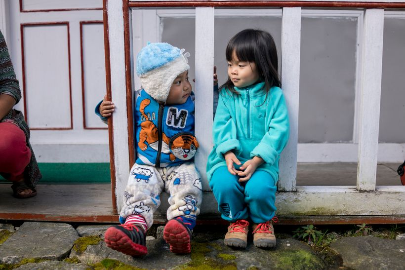 <em>Little Chow cosies up to a fellow local toddler.</em>