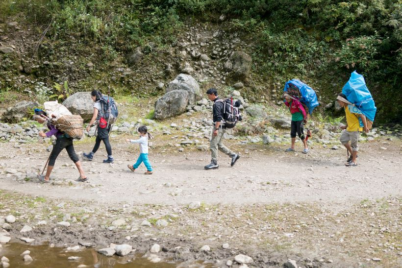 <em>Trekking in the Khumbu Valley, flanked by porters with loads up to 60kg. Porters earn between $10—$15 per day carrying