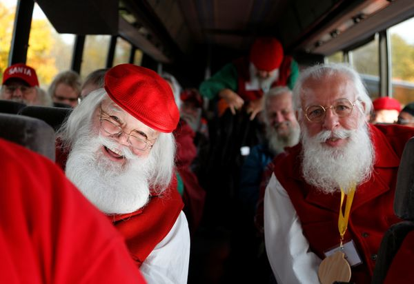 Santas board a bus for a field trip from the Charles W. Howard Santa Claus School in Midland, Michigan.