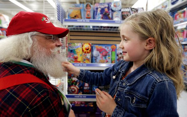 Five year old Claire tugs the beard of Santa Barry Westmoreland of Germanton, North Carolina as the Santas visit a Toys R Us