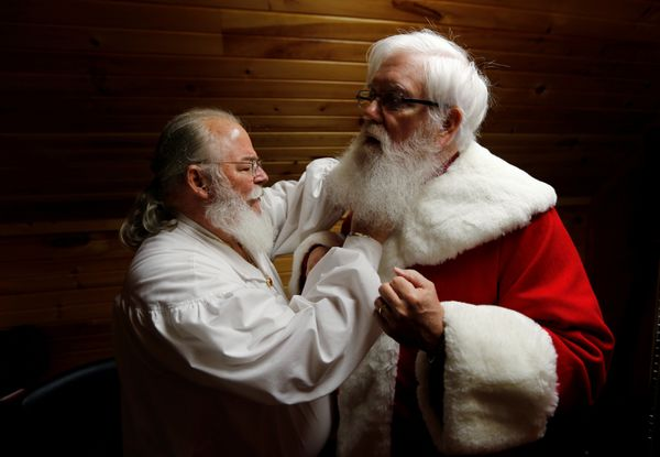 Santa Jim Hastings (R) from Durham, North Carolina, is helped into his suit by a fellow Santa prior to a visit from a group o