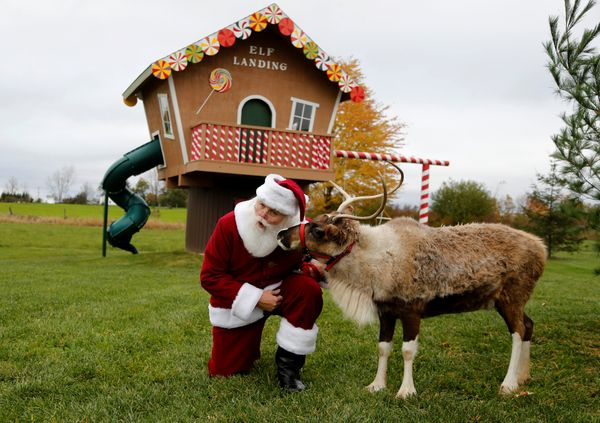 Santa listens to a reindeer at the Rooftop Landing Reindeer Farm in Clare, Michigan.