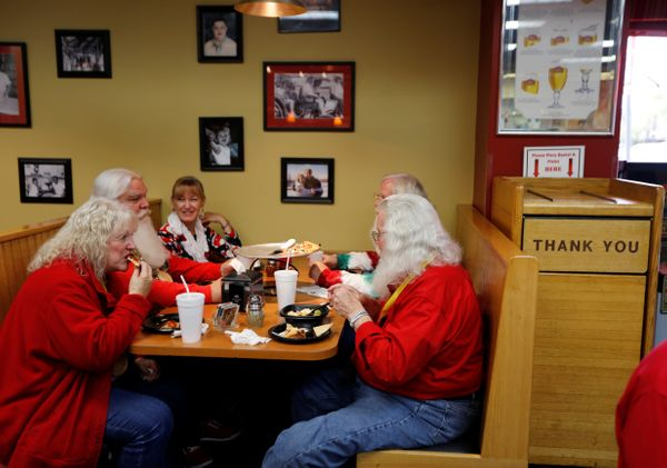 Santas and Mrs. Clauses enjoy lunch at Pizza Sam's on Main Street during a break from class.