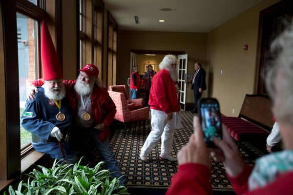 Mrs Claus takes a photo of her husband Santa Bill Armstrong (R), with Santa Fred Osther as they head for class.