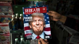TOPSHOT - A copy of the local Chinese magazine Global People with a cover story that translates to 'Why did Trump win' is seen with a front cover portrait of US president-elect Donald Trump at a news stand in Shanghai on November 14, 2016.   Chinese President Xi Jinping and US president-elect Donald Trump agreed November 14 to meet 'at an early date' to discuss the relationship between their two powers, Chinese state broadcaster CCTV said.  / AFP / JOHANNES EISELE        (Photo credit should read JOHANNES EISELE/AFP/Getty Images)