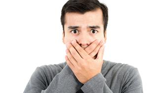 Shocked man with hands covering mouth