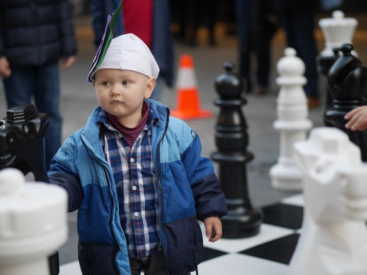 a young chess fan explores the life-size chessboard outside the playing venue