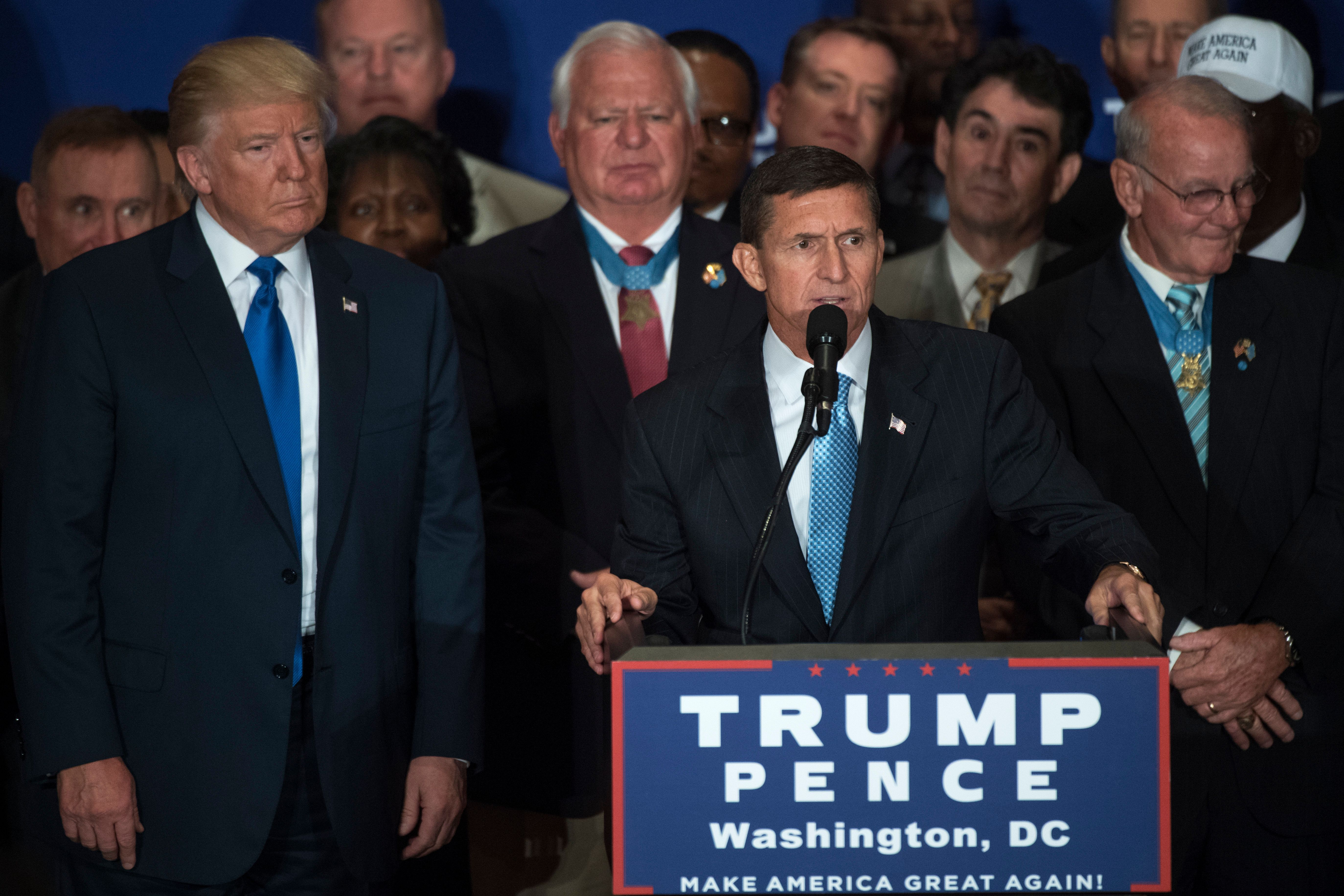 Retired Lt. Gen. Michael Flynn, at podium, and Republican presidential candidate Donald Trump attend a campaign event with ve