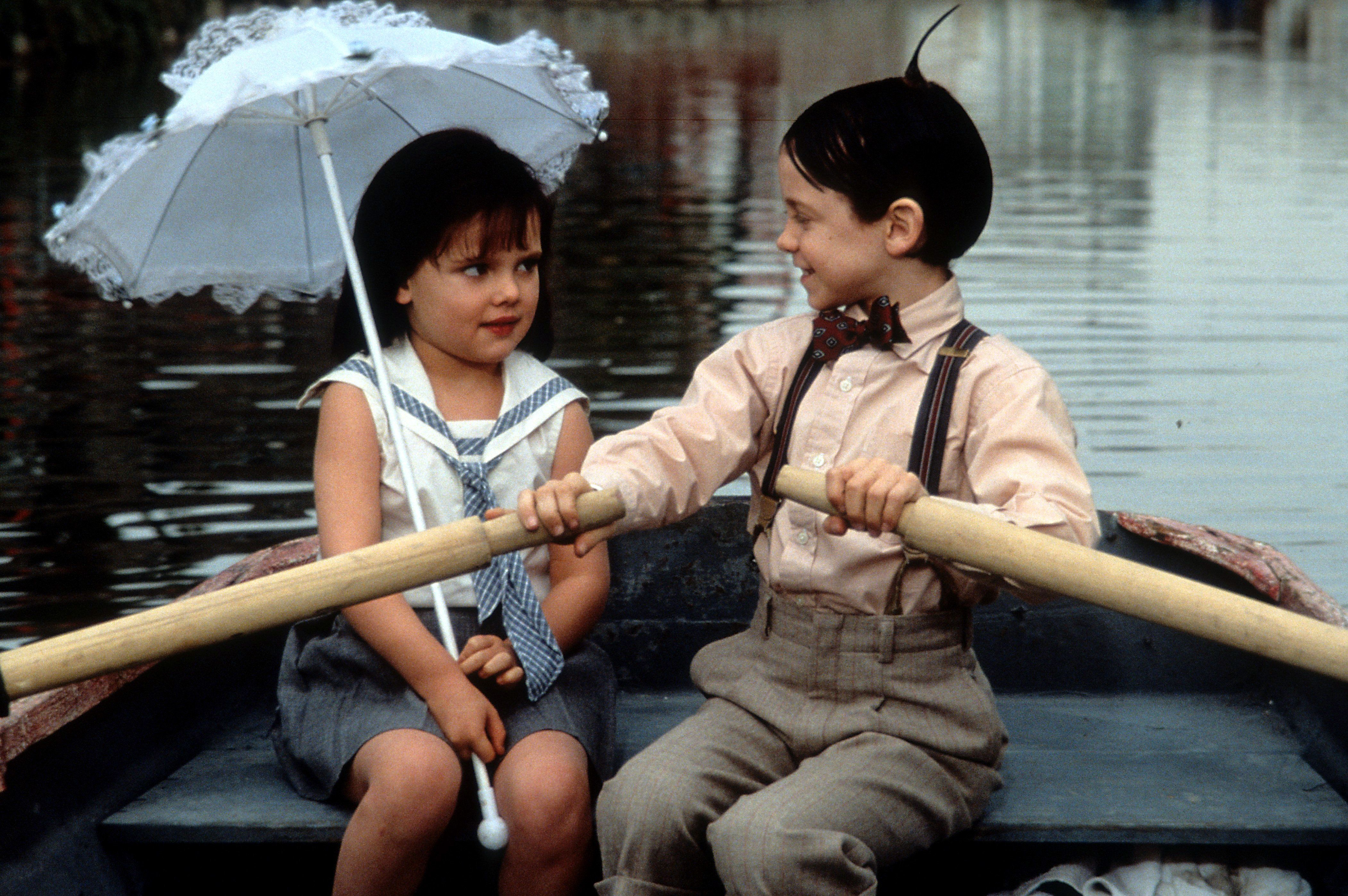 """Bug Hall rowing a boat while looking at Brittany Ashton Holmes in a scene from the film """"The Little Rascals,"""" 1994."""