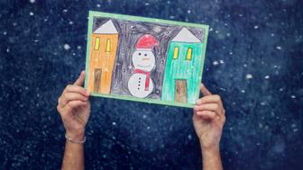 child hands holding a  hand made christmas card with snowman and winter houses,Blue , snow background