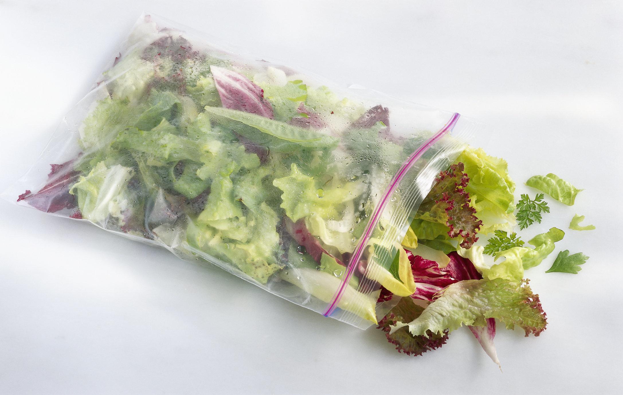 Assorted lettuce in plastic bag, studio shot