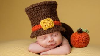 Smiling four week old newborn baby boy wearing a crocheted Pilgrim hat. He is sleeping on a gold blanket next to a crocheted pumpkin.