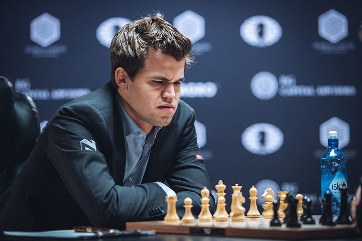 World chess champion Magnus Carlsen frowns at the board during his 8th game against challenger Sergey Karjakin