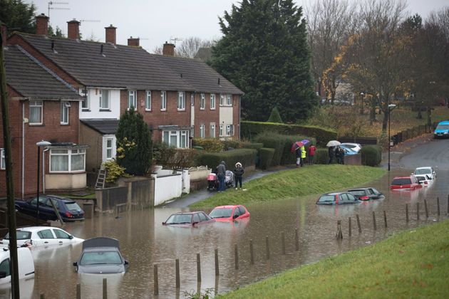 Residents look at cars that have been submerged under several feet of flood water in Hartcliffe