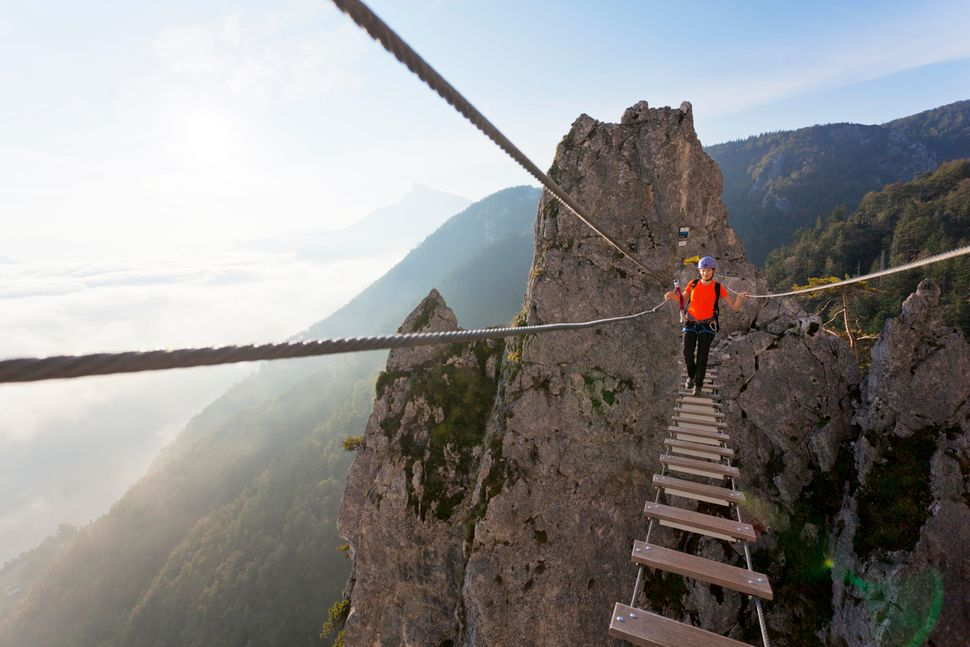 A young woman crosses the Dragon's Wall rope bridge in Mondsee, Austria.