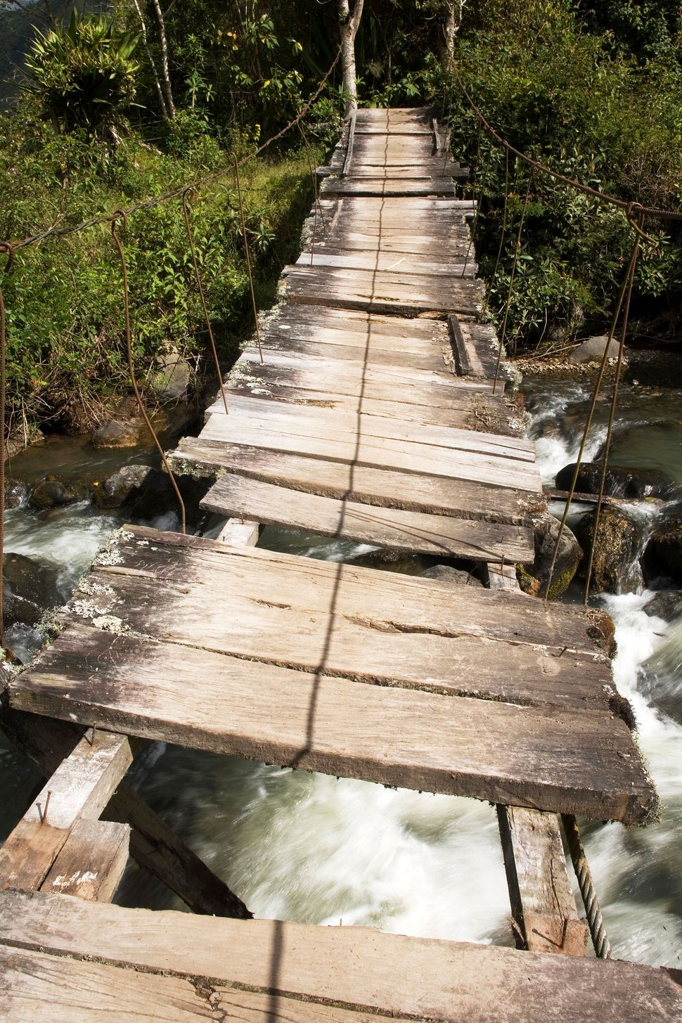 Rope bridge with missing boards in Imbabura, Ecuador.