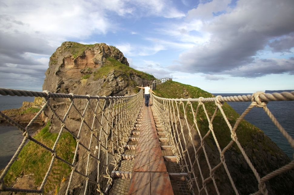 A girl walks over Carrick rope bridge, Ballintoy, County Antrim, Northern Ireland.