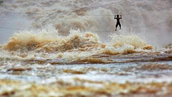 During the rainy season, huge waves dwarf Laotian fisherman Samnieng as he uses a homemade high wire bridge to cross over the dangerous waters of the turbulent Mekong river in order to reach prized fishing grounds on the many river islands situated near the Khone Phapheng Falls (Khone Falls) in the area known as Si Phan Don ('4000 islands'). Champasak Province, Laos