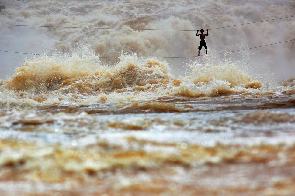During the rainy season, huge waves dwarf Laotian fisherman Samnieng as he uses a homemade high-wire bridge to cross over the