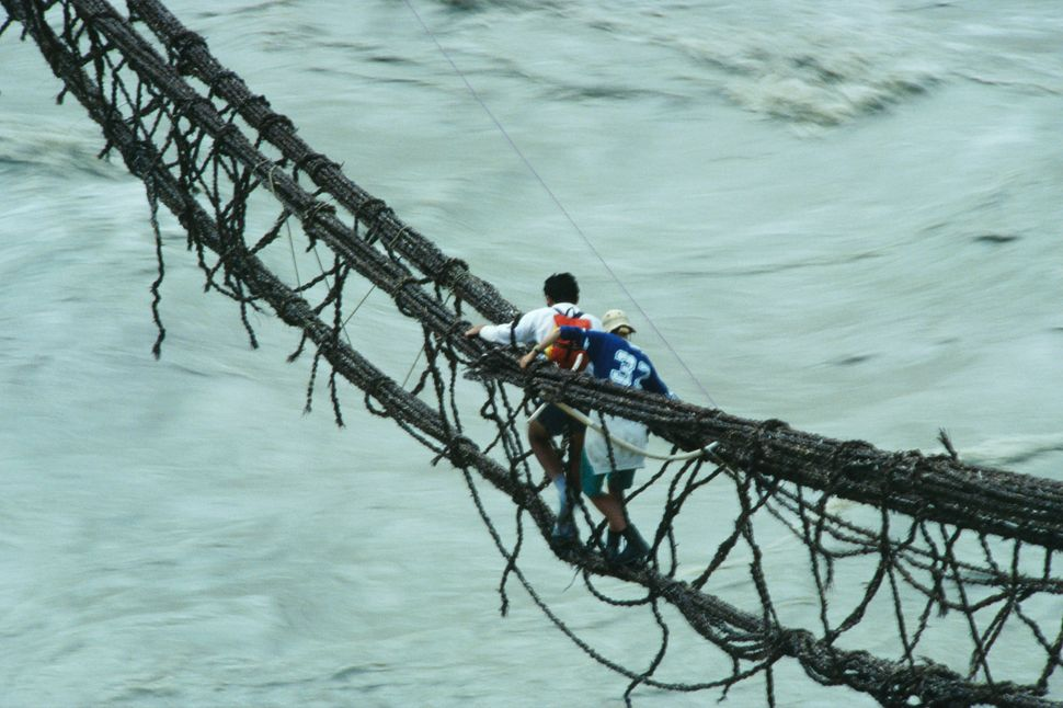 People cross a river on a rope bridge in Askole, Pakistan.