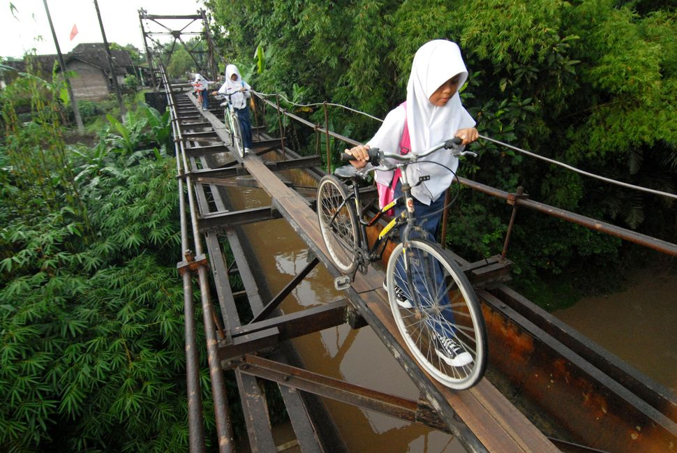 Indonesian students go to school via a suspension bridge that connects the Suro village and Plempungan village in Boyolali, C