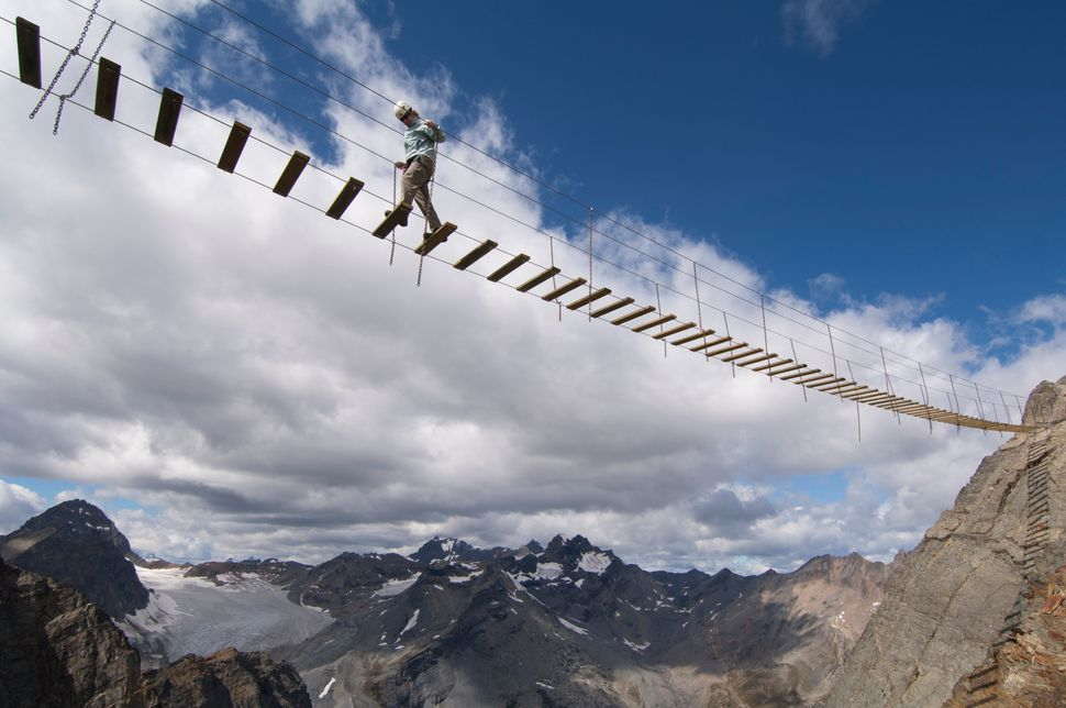 A woman crosses an exposed suspension bridge in British Columbia.