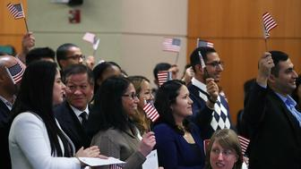 ALEXANDRIA, VA - NOVEMBER 21:  People wave American flags as 165 new U.S. citizens are sworn in during a naturalization ceremony at the U.S. Patent and Trademark Office, on November 21, 2016 in Alexandria, Virginia.  (Photo by Mark Wilson/Getty Images)