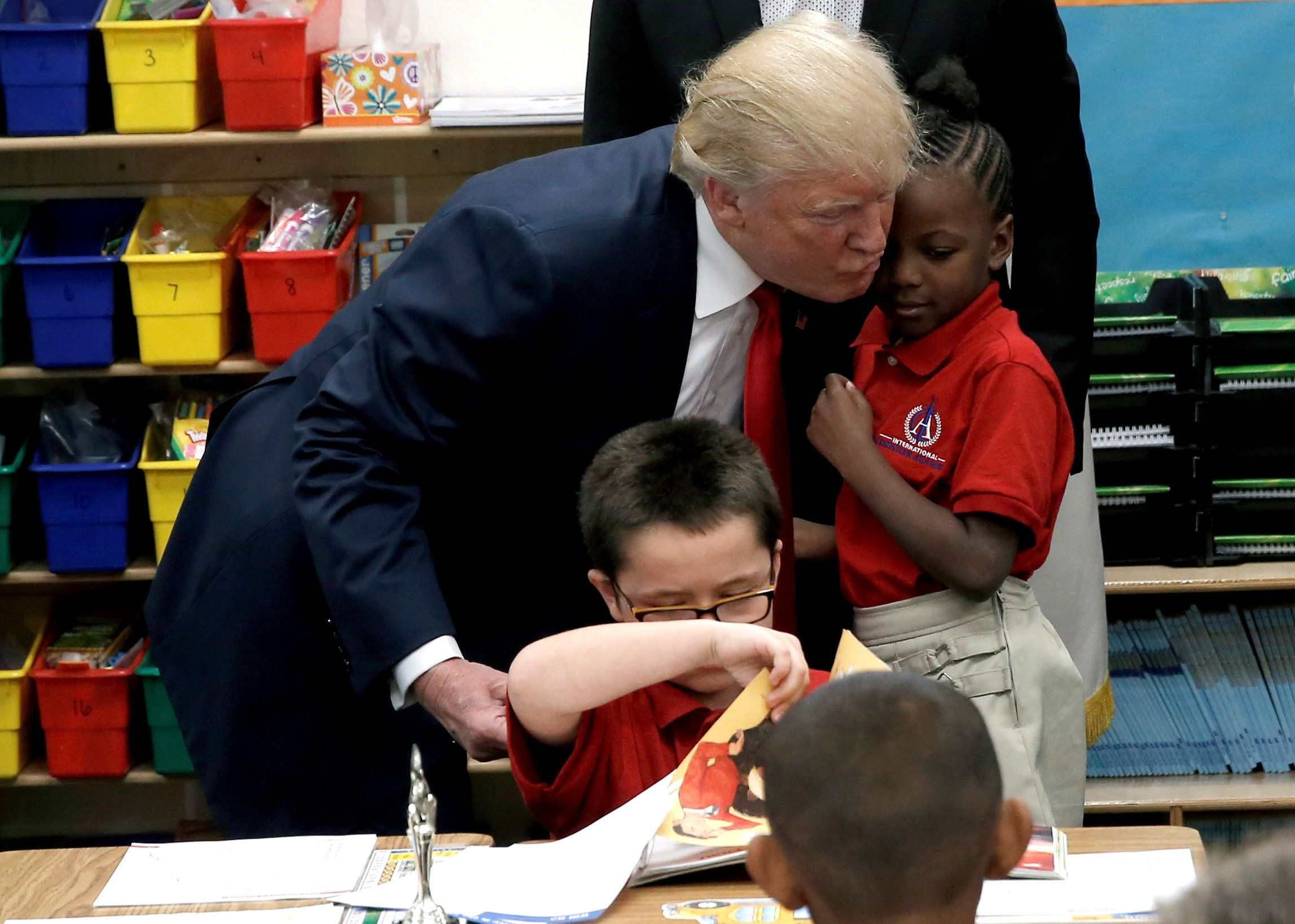 President-elect Donald Trump hugs a student after receiving a Bible as a gift during a campaign visit to the Internation