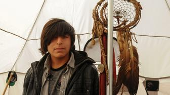 Numpa Bald Eagle, 17, from Eagle Butte Reservation poses for a photograph inside his tent in an encampment during a protest against plans to pass the Dakota Access pipeline near the Standing Rock Indian Reservation, near Cannon Ball, North Dakota, U.S. November 19, 2016. REUTERS/Stephanie Keith
