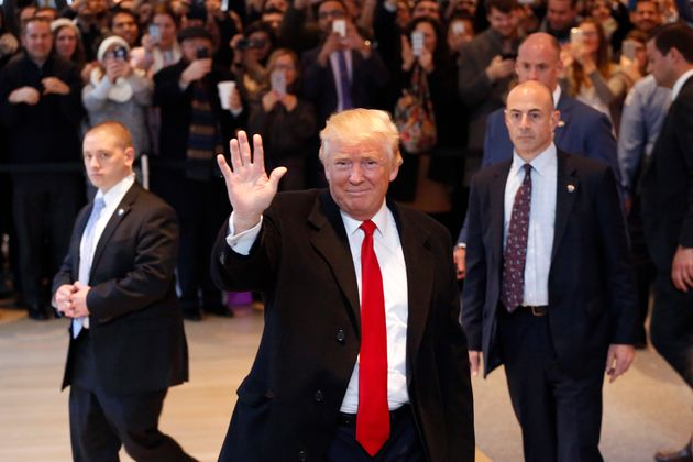 President-elect Donald Trump waves to the crowd as he leaves the New York Times building following a