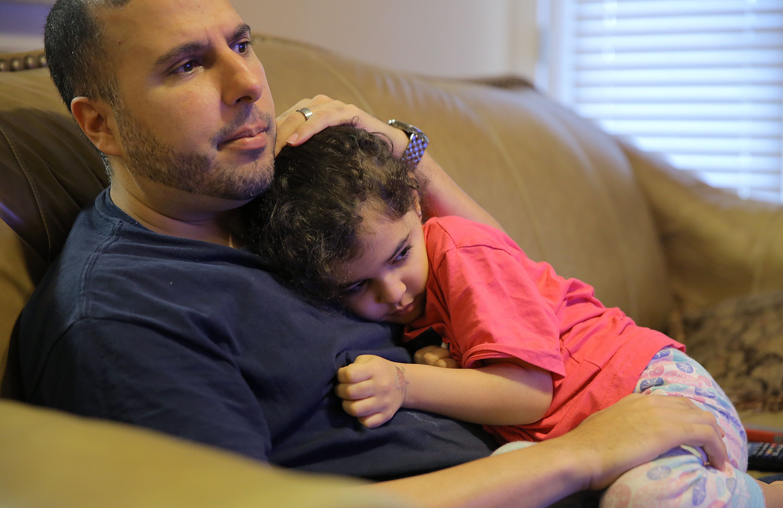 North Carolina resident Shadi Sadi holds his 5-year-old daughter Saja while watching the news at home...